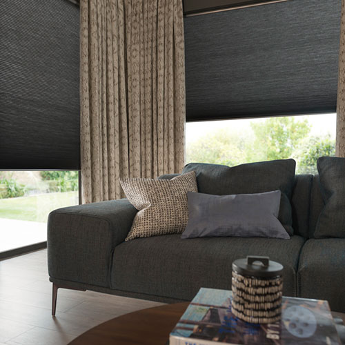 Patterned curtains with grey roman blinds